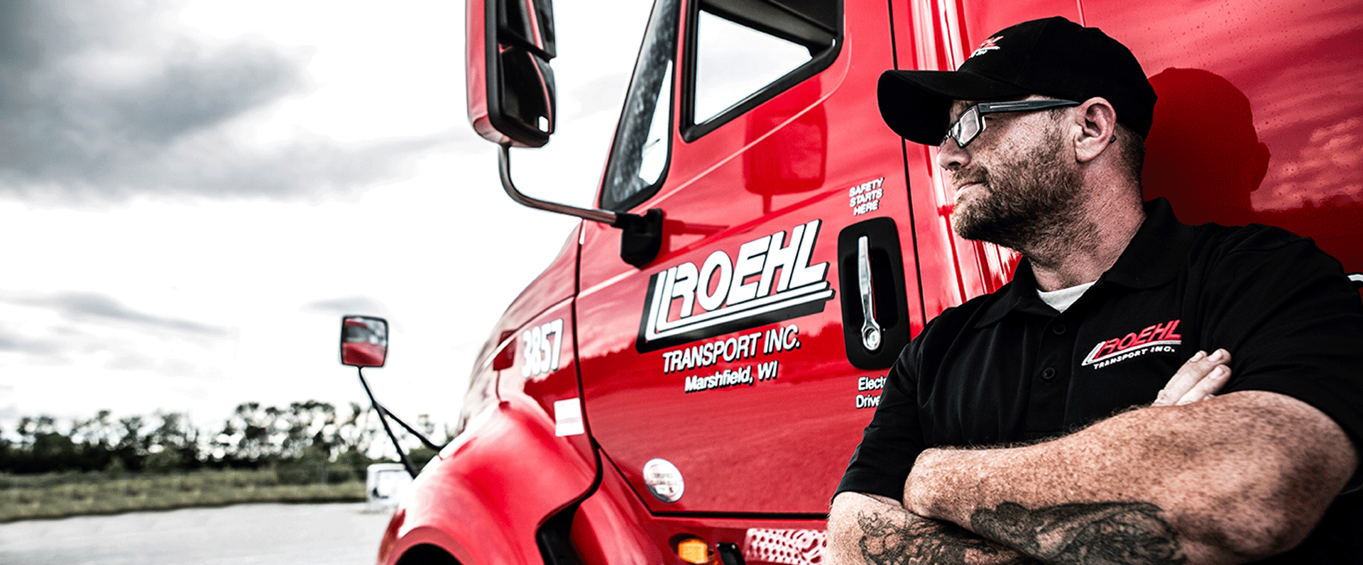 Roehl driver leaning against red truck